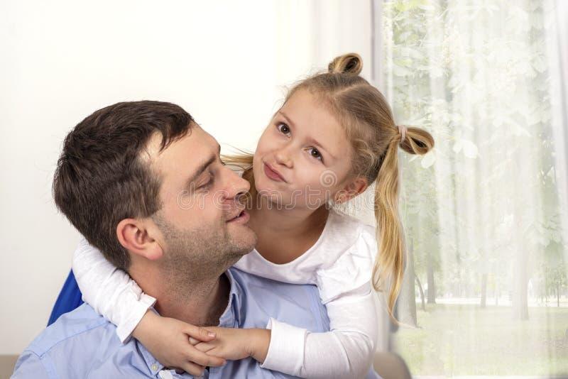 Uma moça que abraça seu pai com uma expressão feliz foto de stock royalty free