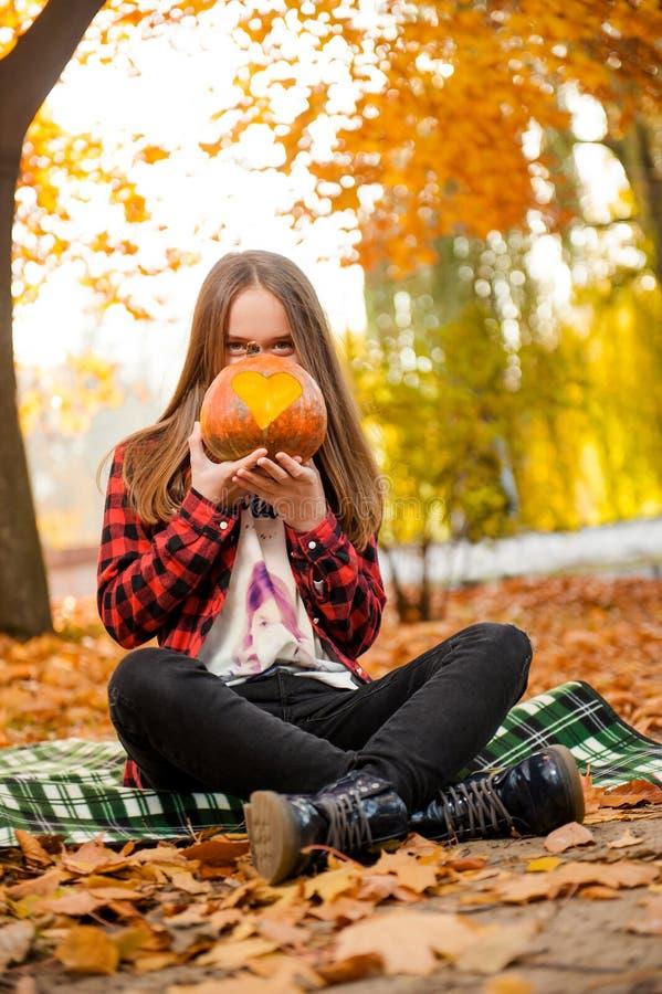 Uma moça que esconde sua cara atrás de uma abóbora fotografia de stock royalty free