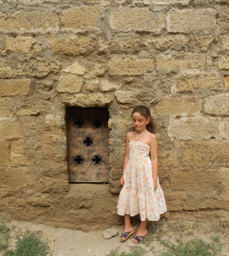 Uma moça que está perto da porta medieval do metal na parede da pedra calcária imagem de stock royalty free