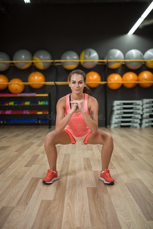 Uma moça que faz ocupas em um fundo colorido do gym Uma mulher maravilhosa com o corpo perfeito que faz exercícios em um gym imagens de stock
