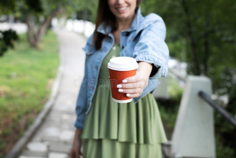 Uma moça que guarda um vidro do café no comprimento do braço foto de stock royalty free