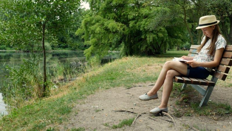 Uma moça que lê um livro em um banco perto do lago fotografia de stock royalty free