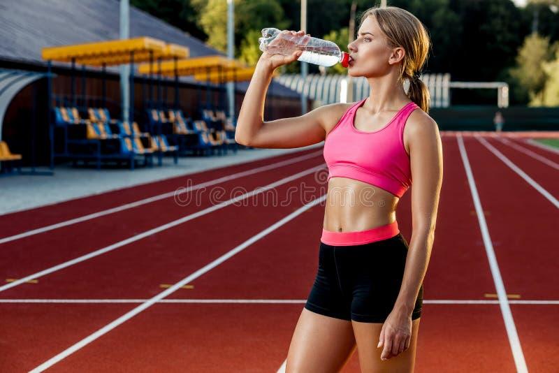 Uma moça que participe no esporte na água potável do estádio fotografia de stock royalty free