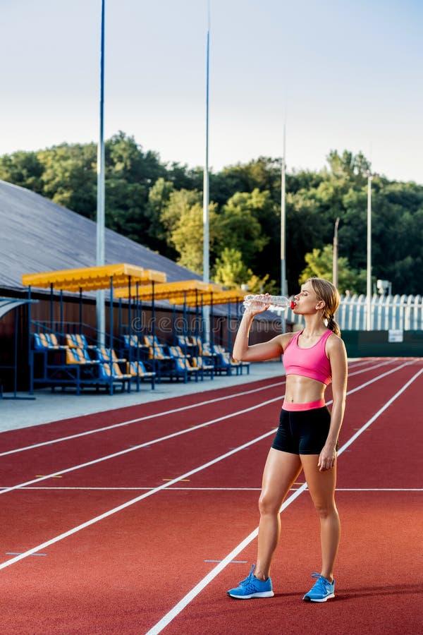 Uma moça que participe no esporte na água potável do estádio imagens de stock