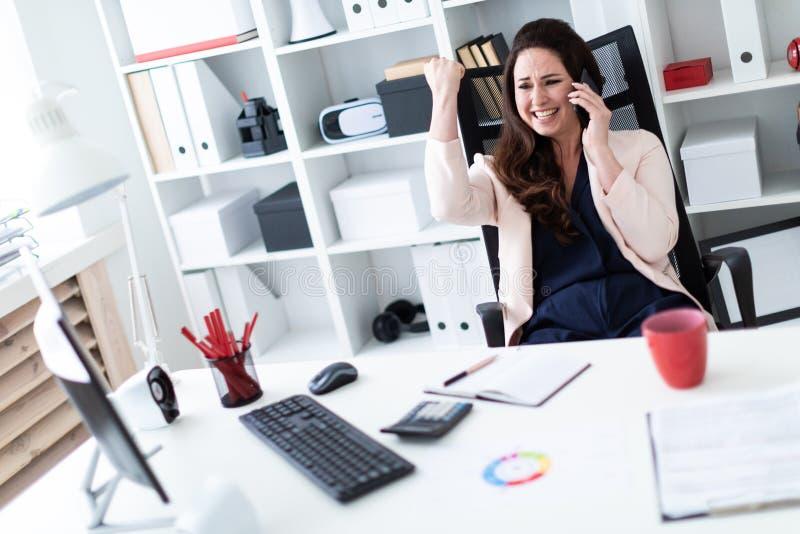 Uma moça que senta-se em uma mesa do computador no escritório, guardando um telefone em uma mão, e a segunda curvatura em um punh fotos de stock