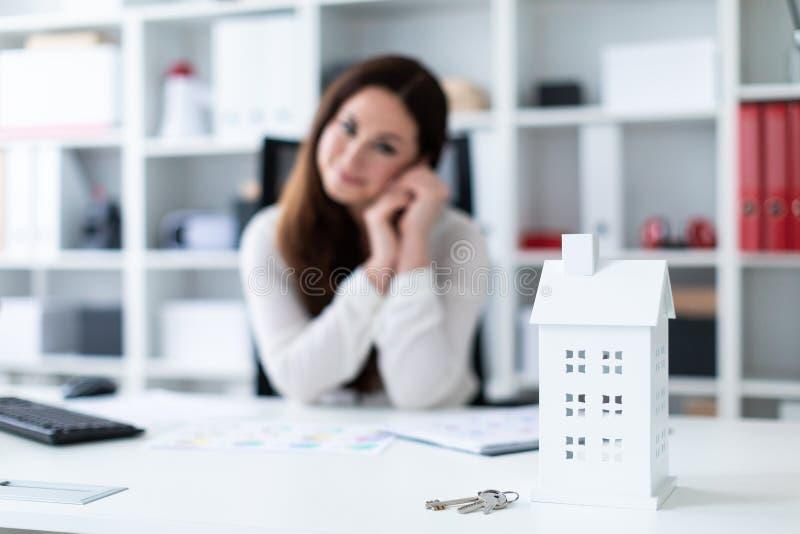 Uma moça que senta-se na tabela A foto com profundidade de campo, destacou o foco na casa e nas chaves fotos de stock royalty free