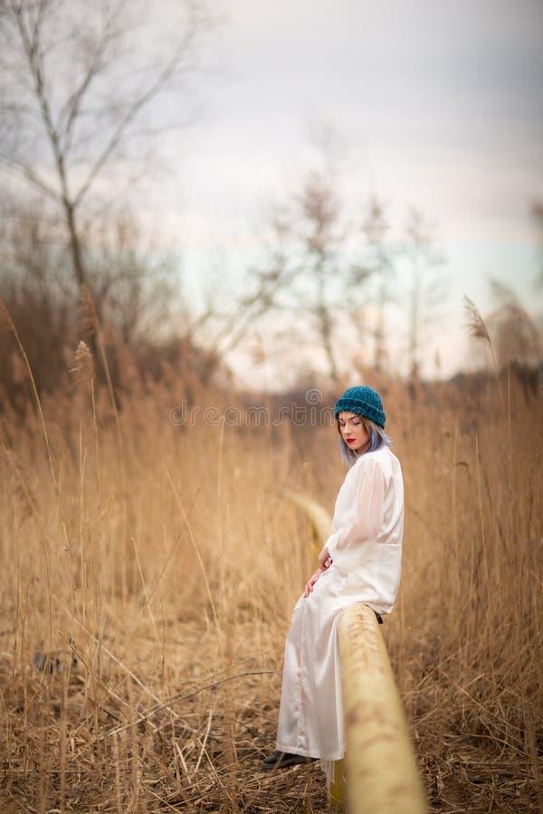 Uma moça vestida em um vestido longo branco, sentando-se em uma tubulação, perto de um campo de trigo fotografia de stock royalty free
