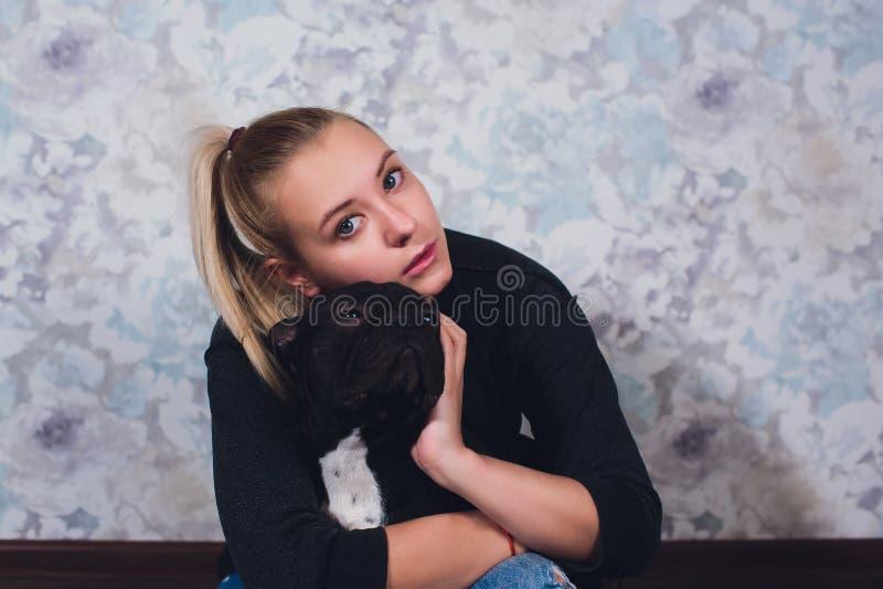 Uma mo?a bonita senta e guarda muito cachorrinho pequeno de um c?o do buldogue franc?s fotografia de stock