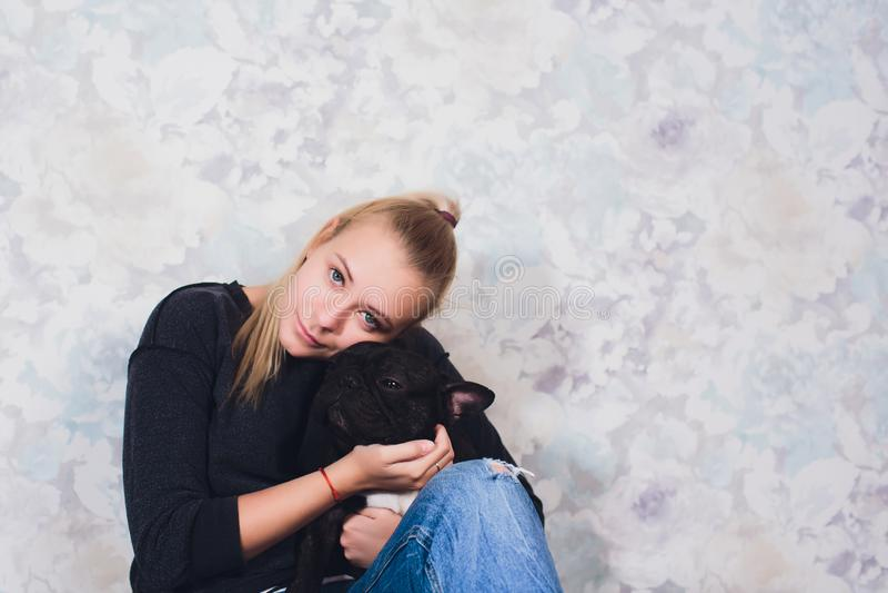 Uma mo?a bonita senta e guarda muito cachorrinho pequeno de um c?o do buldogue franc?s foto de stock