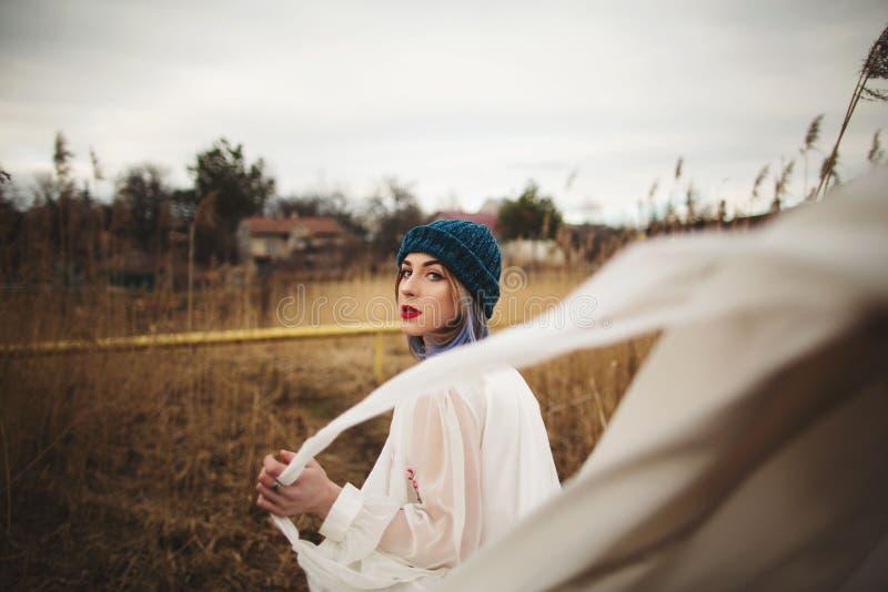 Uma mo?a em um chap?u ? moda e em um vestido branco que anda em um campo de trigo imagens de stock royalty free