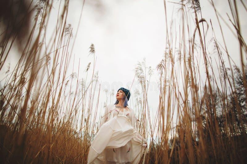 Uma mo?a em um chap?u ? moda e em um vestido branco que anda em um campo de trigo imagem de stock