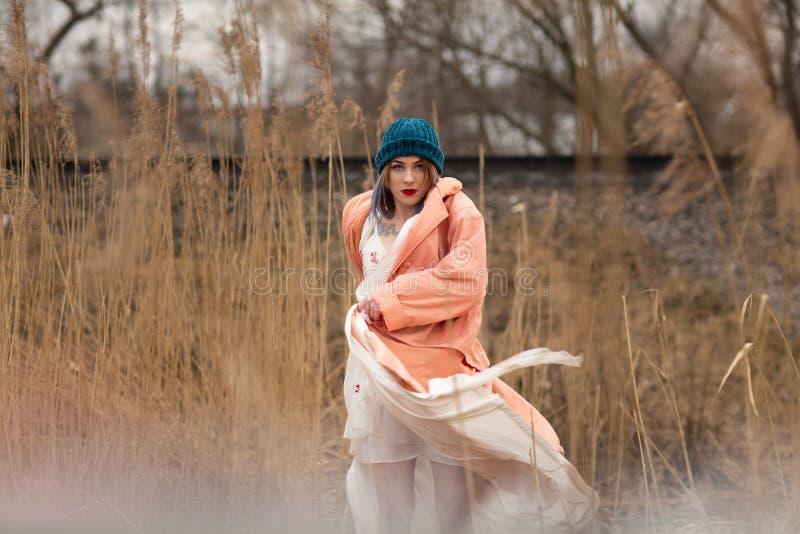 Uma mo?a em um vestido branco bonito e em um chap?u ? moda levanta em um campo de trigo foto de stock