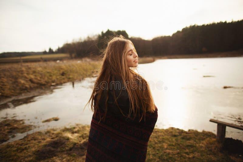 Uma mo?a levanta na costa de um lago, jogando um len?o nela imagens de stock royalty free