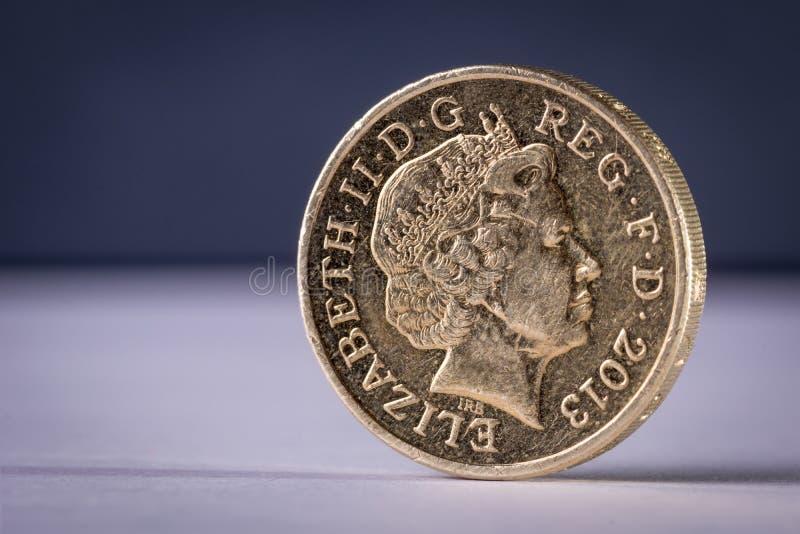 Uma moeda britânica da libra da rainha está o fundo liso fotos de stock