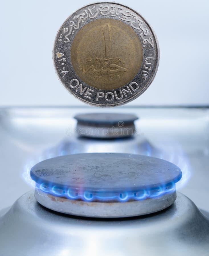 Uma moeda de libra egípcia sobre o queimador de gás fotos de stock royalty free