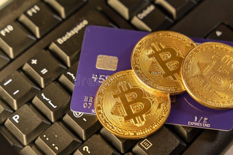 Uma moeda do bitcoin com o cartão de crédito azul sobre o teclado de computador no fundo, cryptocurrency que aceitam para o pagam imagens de stock royalty free