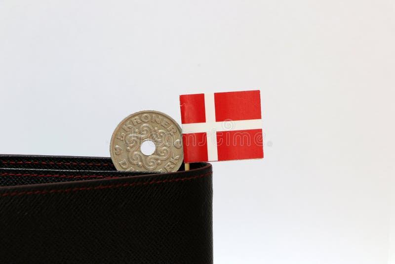 Uma moeda do dinheiro das coroas dinamarquesas e da mini vara da bandeira de Dinamarca na carteira preta com fundo branco fotografia de stock
