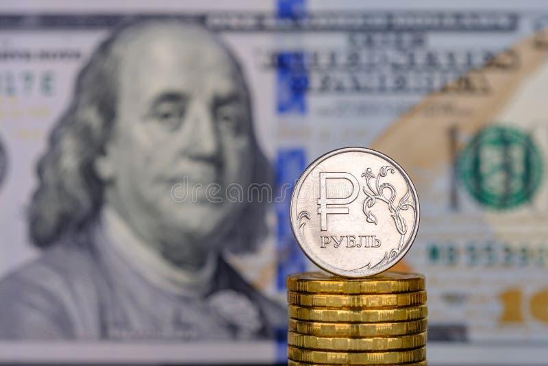 Uma moeda do rublo contra um fundo de 100 dólares de cédulas foto de stock royalty free