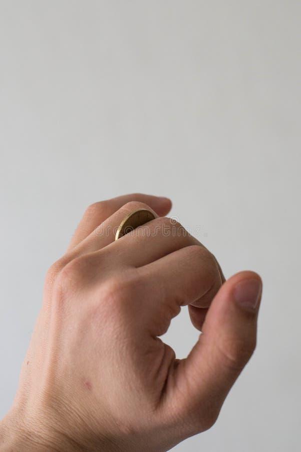 Uma moeda na mão de um homem imagem de stock