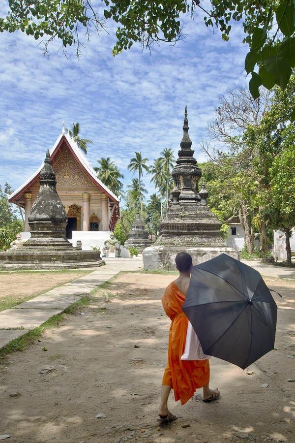 Uma monge budista com guarda-chuva anda para o templo de Wat Aham de Luang Prabang, Laos imagens de stock