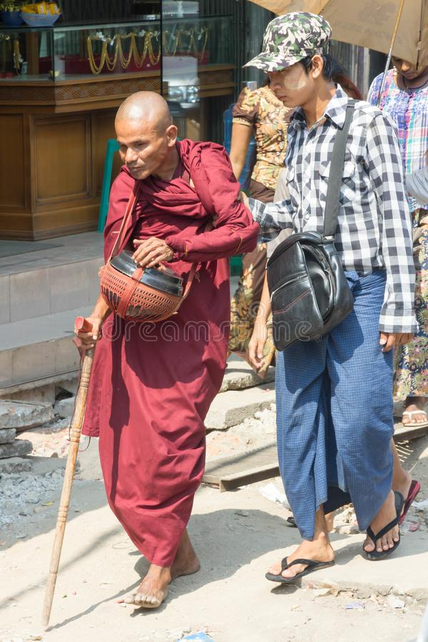 Uma monge cega é ajudada através da estrada fotos de stock