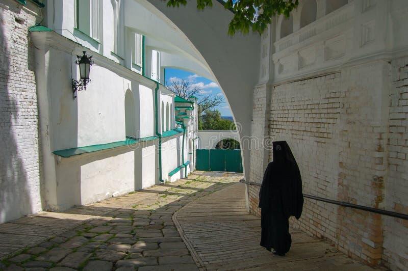 Uma monge em uma veste preta em um monastério ucrânia O Kiev Pechersk Lavra é um nome comum para um complexo inteiro das catedrai imagem de stock royalty free