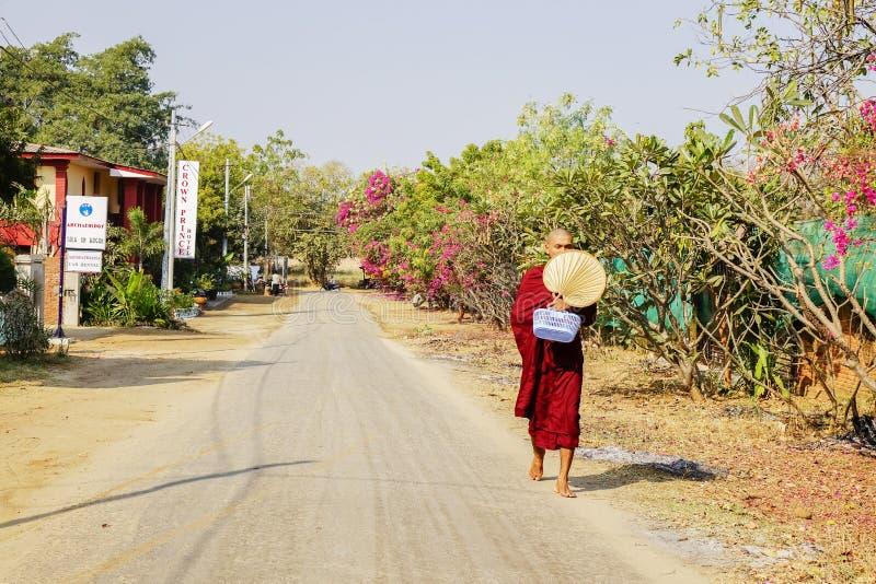 Uma monge está andando na estrada em Bagan, Myanmar imagem de stock