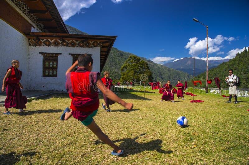 Uma monge nova disparou em um objetivo, monges joga o futebol Trashiyangtse Dzong, Butão oriental imagens de stock