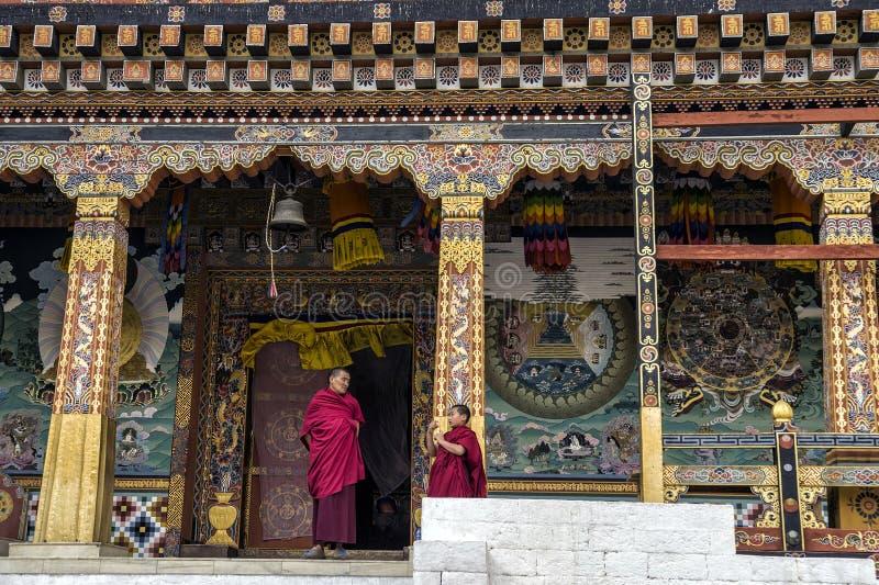 Uma monge superior e júnior na discussão durante o tempo da ruptura em Tashichho Dzong Bhuitan foto de stock