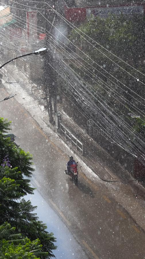 Uma montada da pessoa scooty na chuva em Nepal imagem de stock royalty free