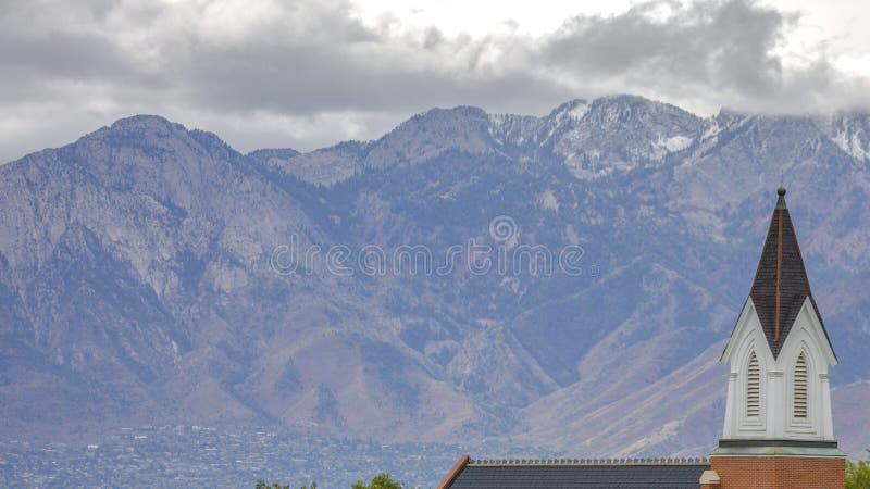 Uma montanha de negligência e nuvens da torre da igreja imagens de stock royalty free