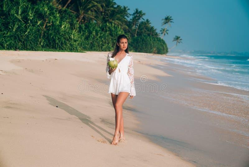Uma morena bonita nos macacões brancos da praia anda ao longo do litoral, admira a praia branca arenosa, veste à moda imagem de stock