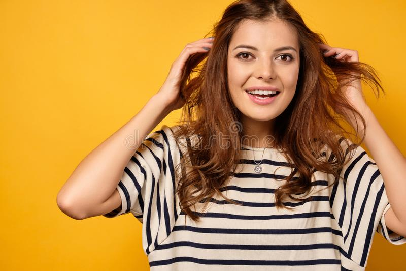 Uma morena em uma camiseta listrada sobre um fundo amarelo, olha alegremente para a câmera, jogando cabelo fora imagem de stock royalty free