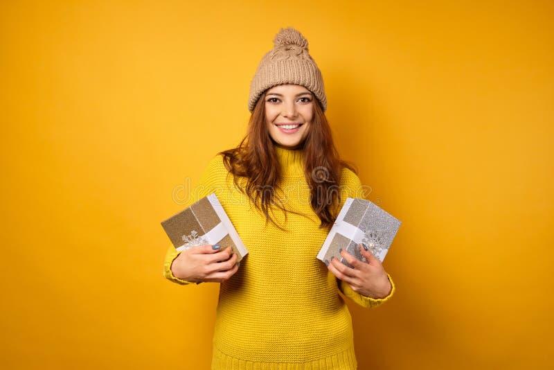 Uma morena em um suéter amarelo e um chapéu em fundo amarelo, sorrindo alegremente, guarda caixas de presentes fotos de stock