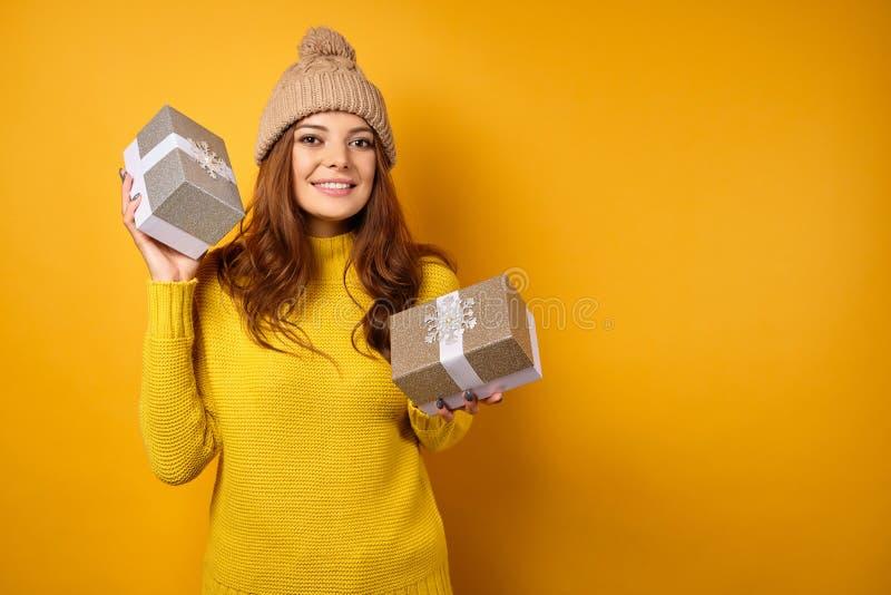 Uma morena em um suéter amarelo e um chapéu em fundo amarelo sorrindo enquanto segurava caixas de presentes fotografia de stock royalty free