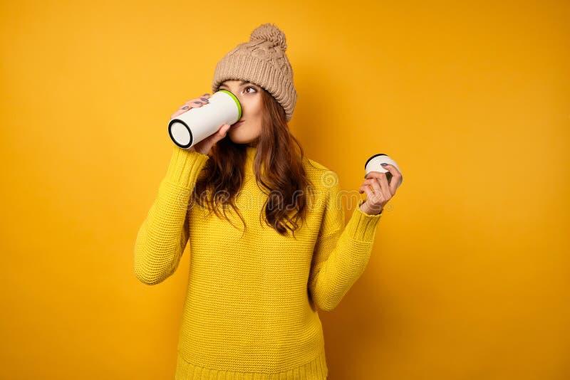 Uma morena em um suéter amarelo e um chapéu em fundo amarelo e toma um gole de um termocopo branco imagem de stock