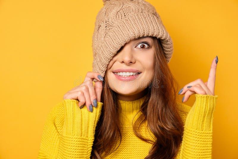 Uma morena em um suéter amarelo se coloca sobre um fundo amarelo, puxando um chapéu sobre um olho e sorrindo, aponta um dedo para foto de stock