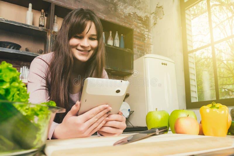 Uma morena nova na cozinha ensolarada da manhã com uma janela prepara o alimento saudável Mulher que usa a tabuleta digital imagens de stock