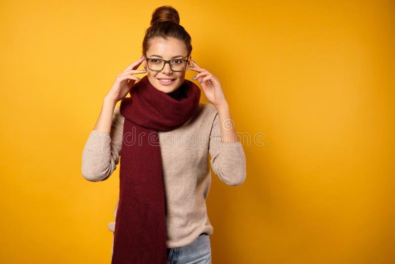 Uma morena num lenço com um feixe alto se posiciona sobre um fundo amarelo ajustando seus óculos foto de stock royalty free