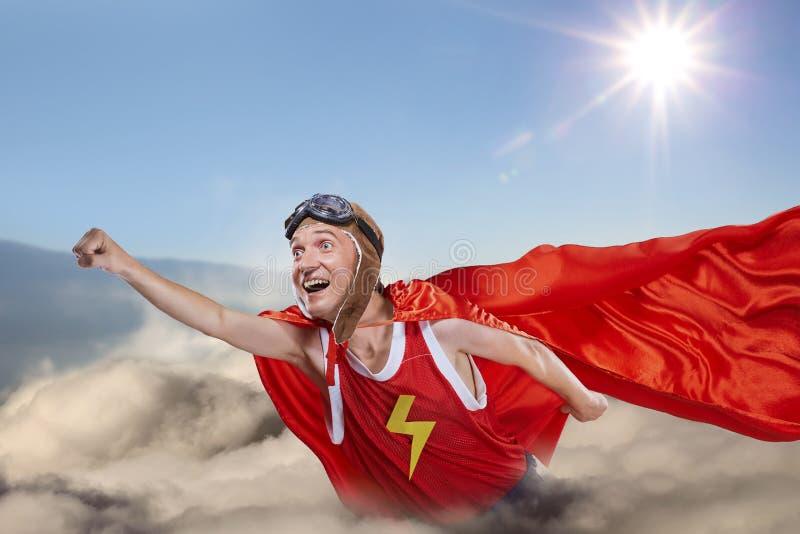 Uma mosca engraçada do super-herói acima das nuvens no céu foto de stock