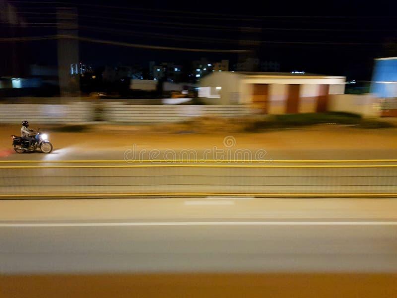 Uma motocicleta movente rápida em estradas de Bangalore fotografia de stock royalty free