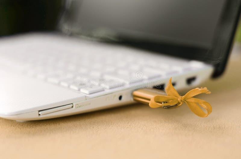 Uma movimentação instantânea alaranjada de USB com uma curva é conectada a um portátil branco, que se encontre em uma cobertura d foto de stock