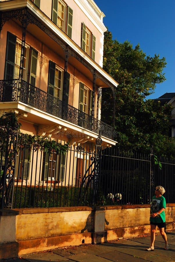Uma mulher adulta anda após casas Antebellum imagens de stock