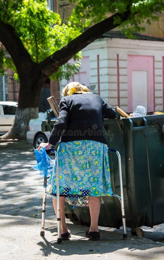 Uma mulher adulta joga para fora o lixo imagens de stock royalty free