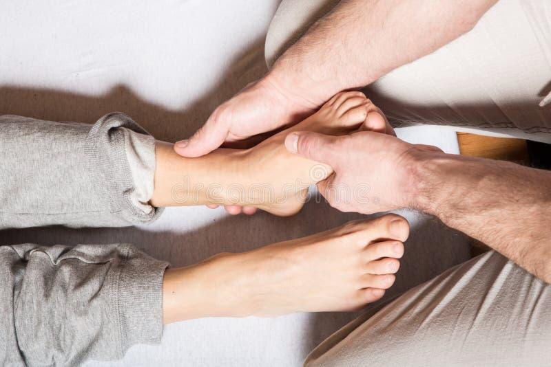 Uma mulher adulta nova que recebe uma massagem do pé imagens de stock