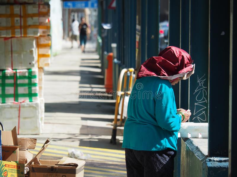 Uma mulher adulta que trabalha nas ruas de Kowloon e que veste um pano em sua cabeça para proteger fotografia de stock