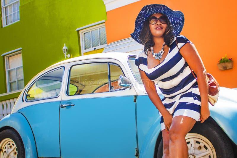 Uma mulher africana bonita em um vestido listrado azul e branco que modela na frente de um vintage Volkswagen Beetle e da casa tr fotos de stock