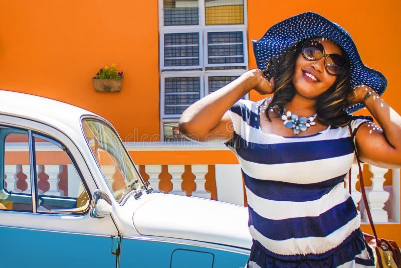Uma mulher africana bonita em um vestido listrado azul e branco que modela na frente de um vintage Volkswagen Beetle e da casa tr foto de stock royalty free