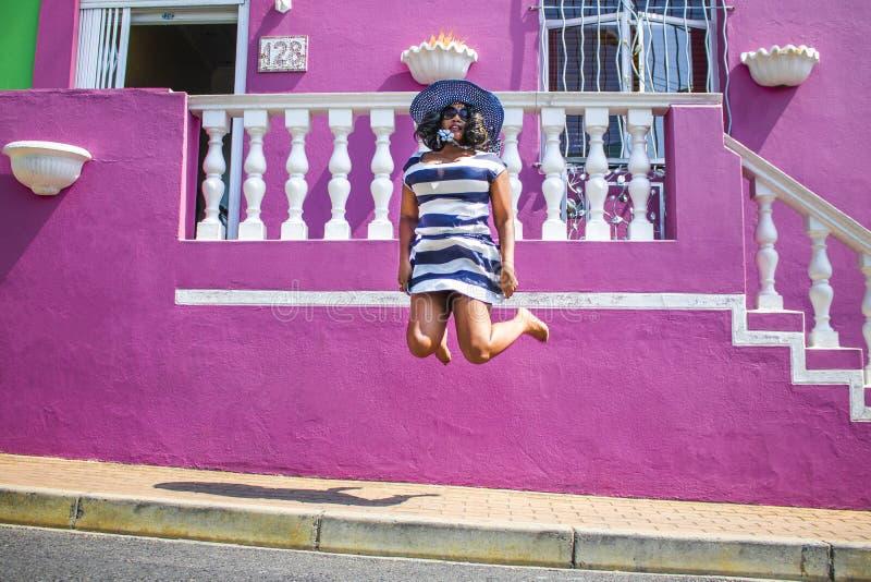 Uma mulher africana bonita em um vestido listrado azul e branco que salta na frente de uma casa tradicional com paredes cor-de-ro imagem de stock royalty free