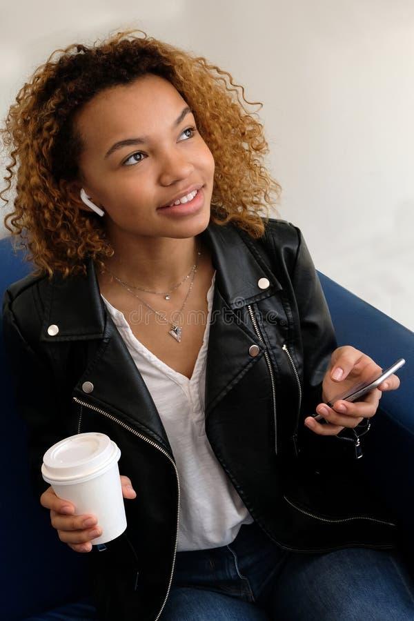 Uma mulher afro-americano nova moderna bonita em um casaco de cabedal com um fone de ouvido sem fio está guardando um vidro branc imagem de stock